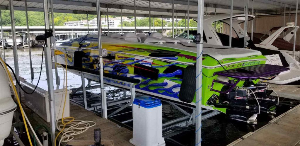 Brightly colored hi-performance boat docked on LOTO Lift's LT (Lifetime) Model boat lift bunks