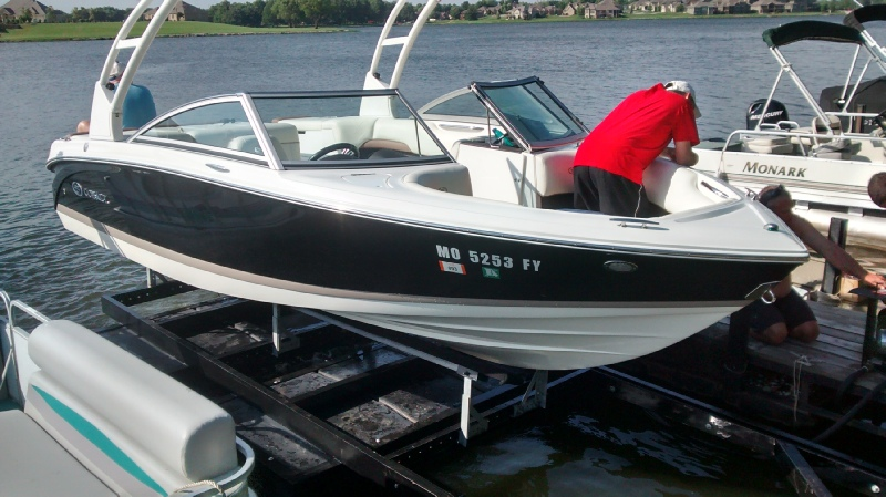Man in a speed boat docked on a front mount life.