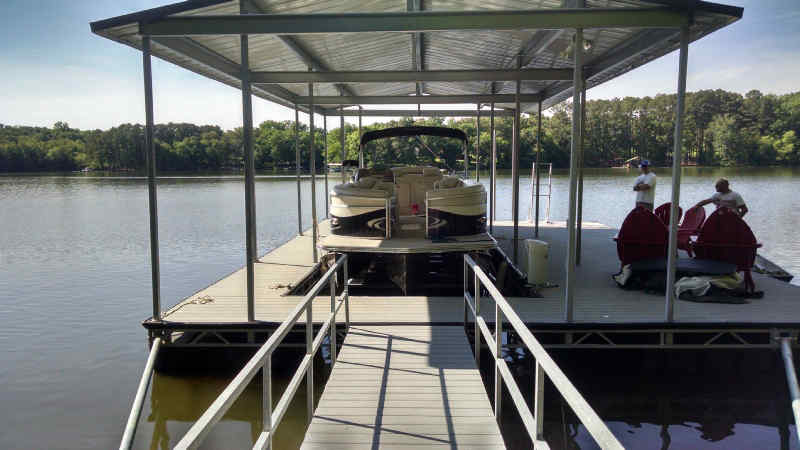 Pontoon boat on shallow water boat lift.