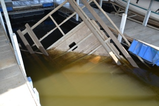 Sinking boat lift in muddy water in a boat dock.