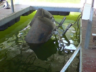 Damaged boat lift sinking in a dock slip.