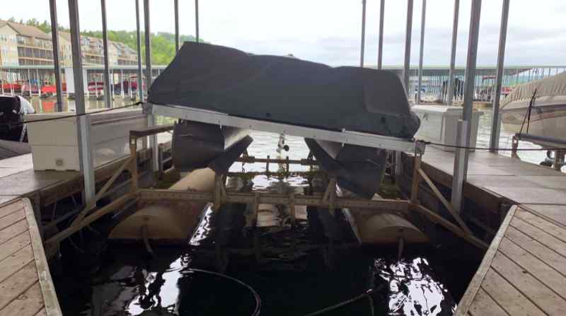 A boat sitting crooked on a defective used boat lift at Lake of the Ozarks