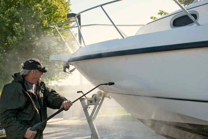 Caucasian man power washing boat