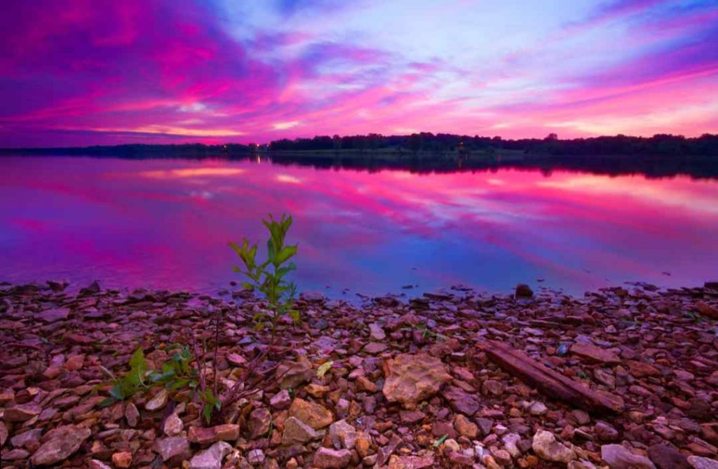 A beautiful pre-dawn sunrise of Longview Lake located just outside of Kansas City with a rocky foreground