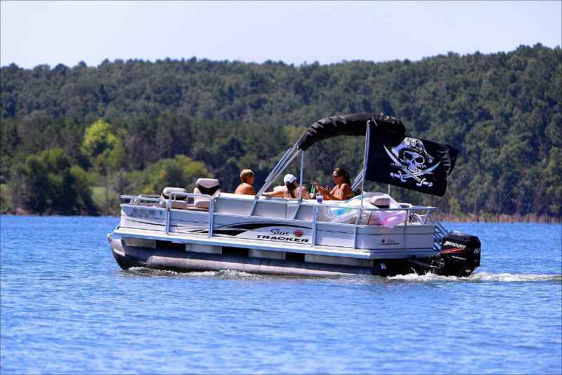 Pontoon boat with a pirate flag cruising on the lake with people relaxing inside
