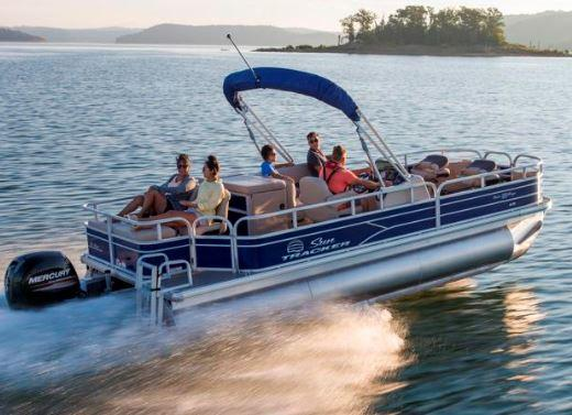 Pontoon boat with passengers speeding across a lake in Missouri