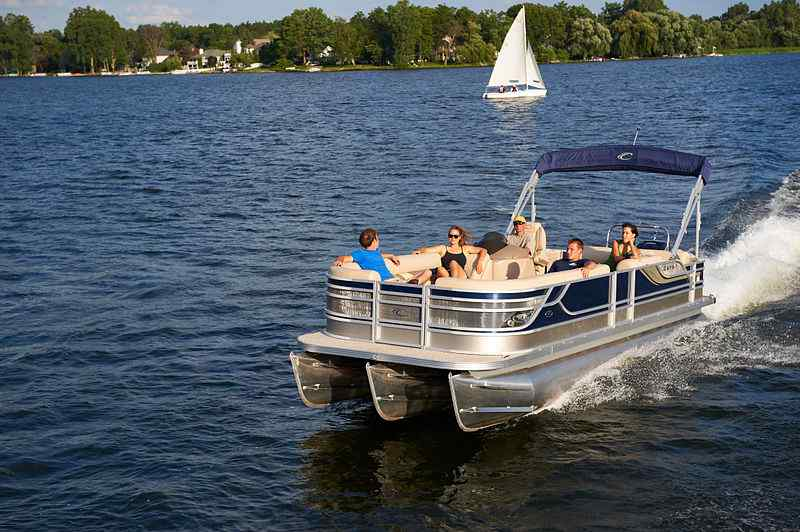 A family in a tritton boat on a lake, with a sailboat in the background