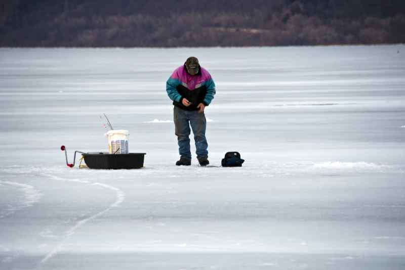 Man ice fishing on frozen Lake of the Ozarks where docks and boat lifts were damaged.