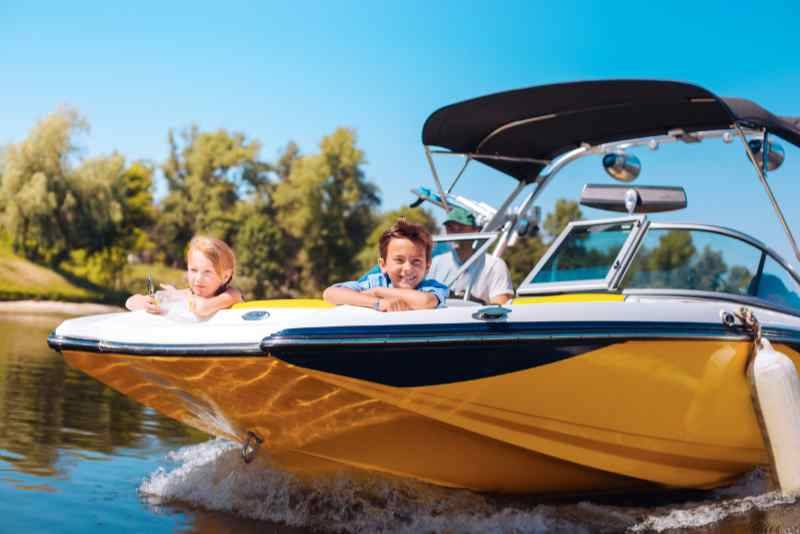 Joyful little LOTO boating siblings sitting on the bow of the boat and contemplating the view while smiling happily