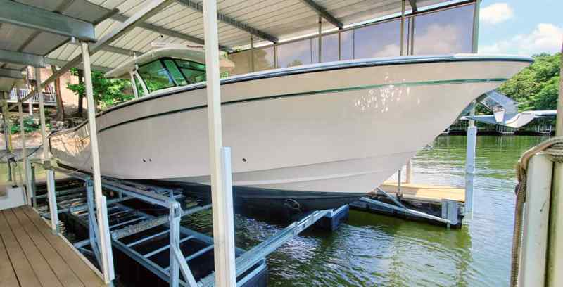 Nice, large boat sits safely on a floating boat lift for sale in Lake Ozark, MO.